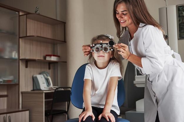 Привлекательная женщина-врач улыбается, любя свою работу. маленькая девочка в очках сидит в клинике и проверяет ее глаза.