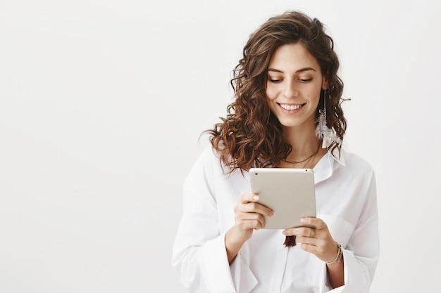 デジタルタブレットを見て魅力的な笑顔の女性起業家
