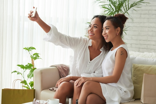 自宅のソファに座って、ソーシャルメディアに投稿するために自分撮りを取っている魅力的な笑顔の女性の友人