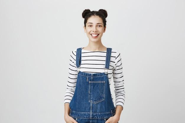 Привлекательная улыбающаяся студентка, выглядящая оптимистичной