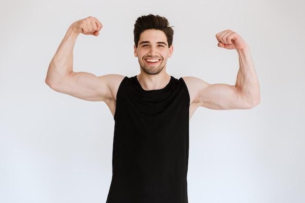 魅力的な笑顔は、白い壁の上に孤立して立っている若いスポーツマンにフィットし、筋肉を曲げる