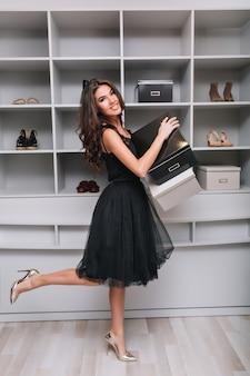 Attraente ragazza sorridente ha comprato scarpe nuove, tenendo le scatole in mano, in piedi in spogliatoio, guardaroba. sta guardando, una gamba in alto. indossa un abito nero soffice e tacchi alti d'argento.