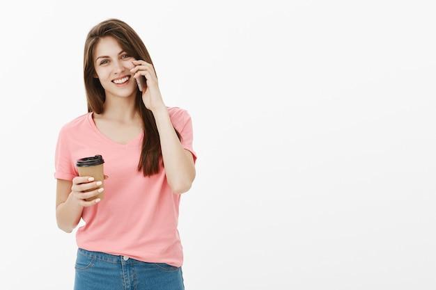 Привлекательная улыбающаяся девушка счастливо разговаривает по телефону и пьет кофе