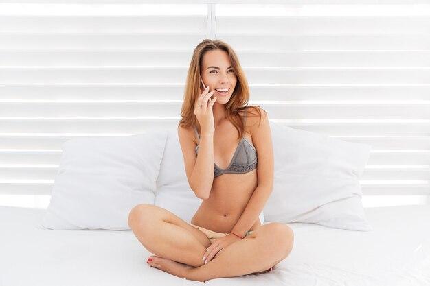 Привлекательная улыбающаяся девушка в бикини разговаривает по телефону с подушками