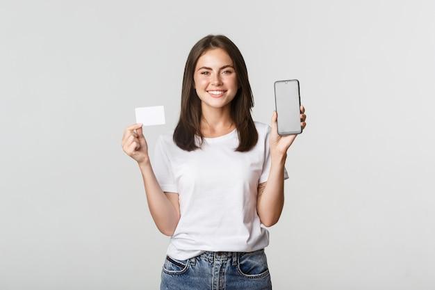 Привлекательная улыбающаяся девушка смотрит довольным и показывает кредитную карту, экран мобильного телефона.