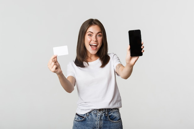 Привлекательная улыбающаяся девушка выглядит довольной и показывает кредитную карту