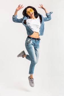 Attraente donna felice sorridente attivo saltando tutta la lunghezza in scarpe da ginnastica isolate su bianco