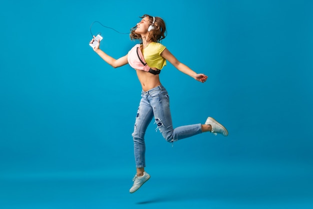 Attractive smiling happy woman dancing listening to music in headphones dressed in hipster stylish outfit isolated on blue studio background, wearing colorful clothes