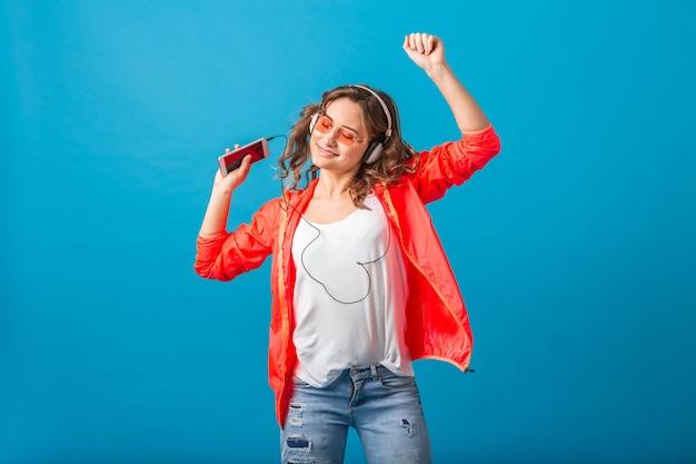 핑크 재킷과 선글라스를 착용, 블루 스튜디오 배경에 고립 된 힙 스터 스타일의 옷을 입고 헤드폰에서 음악을 듣고 춤을 매력적인 웃는 행복 한 여자