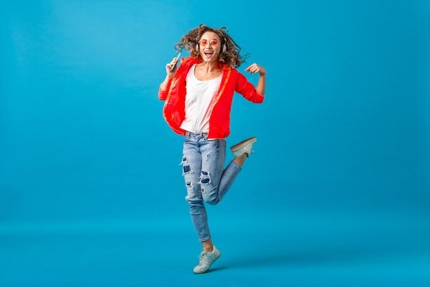 ピンクのジャケットとサングラスを身に着けて、青いスタジオの背景に分離されたヒップスタースタイルの衣装に身を包んだヘッドフォンで音楽を聴いて踊る魅力的な笑顔の幸せな女性