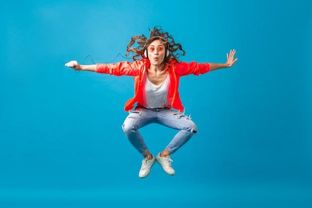 Привлекательная улыбающаяся счастливая женщина танцует, слушая музыку в наушниках, одетая в одежду стиля хипстера, изолированную на синем фоне студии, в розовой куртке и солнцезащитных очках