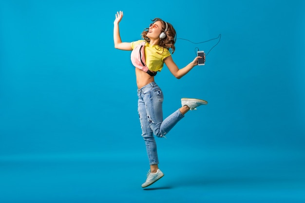Привлекательная улыбающаяся счастливая женщина танцует, слушая музыку в наушниках, одетая в стильный хипстерский наряд на синем фоне студии, в красочной одежде