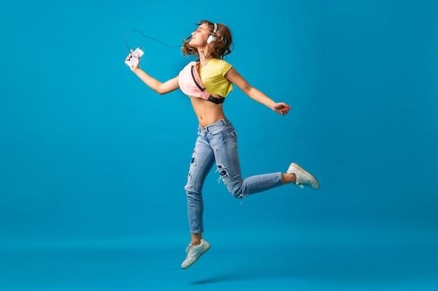 カラフルな服を着て、青いスタジオの背景に分離された流行に敏感なスタイリッシュな衣装に身を包んだヘッドフォンで音楽を聴いて踊る魅力的な笑顔の幸せな女性