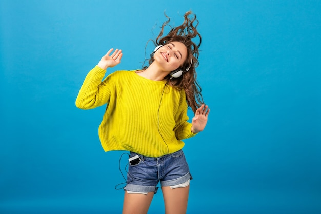ショートパンツと黄色のセーターを着て、青いスタジオの背景に分離されたヒップスターのスタイリッシュな衣装でヘッドフォンで音楽を聴いて踊る魅力的な笑顔の幸せな女性