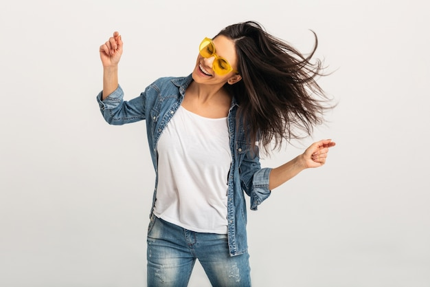白いスタジオで隔離の長い髪を振って踊る魅力的な笑顔の幸せな女性