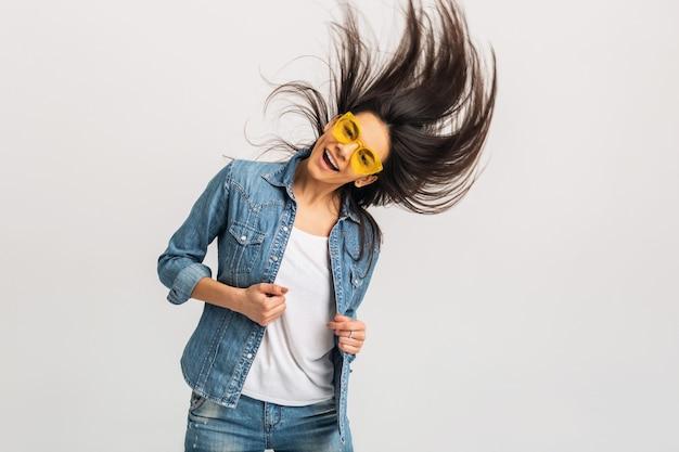 Привлекательная улыбающаяся счастливая женщина танцует, размахивая длинными волосами, изолированными на белой студии