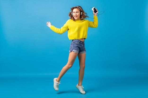 Привлекательная улыбающаяся счастливая женщина прыгает, танцует, слушая музыку в наушниках в хипстерском наряде, изолированном на синем фоне студии, в шортах и желтом свитере