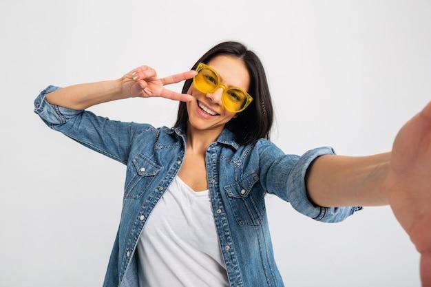 화이트 스튜디오에 고립 된 selfie 사진을 만드는 매력적인 웃는 행복 한 여자