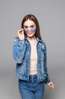 Attractive smiling happy woman making selfie photo isolated on white studio wall dressed jeans and denim shirt wearing yellow sunglasses hipster style outfit