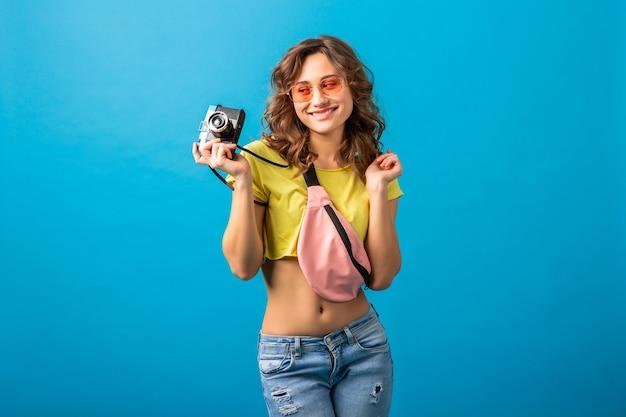 Attraente donna felice sorridente in posa con la macchina fotografica d'epoca scattare foto vestita in abito colorato estate hipster isolato su sfondo blu studio