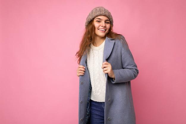 Привлекательная улыбающаяся счастливая молодая брюнетка женщина, стоящая изолирована на красочном фоне, носящем стену