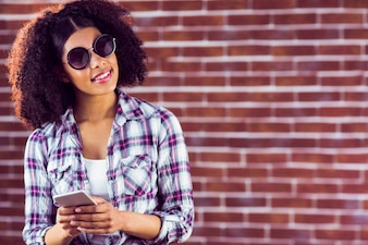 Attractive smiling hipster holding smartphone