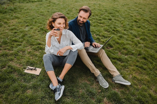 Привлекательный улыбающийся мужчина и женщина разговаривают, сидя на траве в городском парке, делая заметки