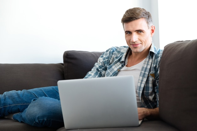 Attractive smiling man in checkered shirt and jeans sitting on sofa and using laptop
