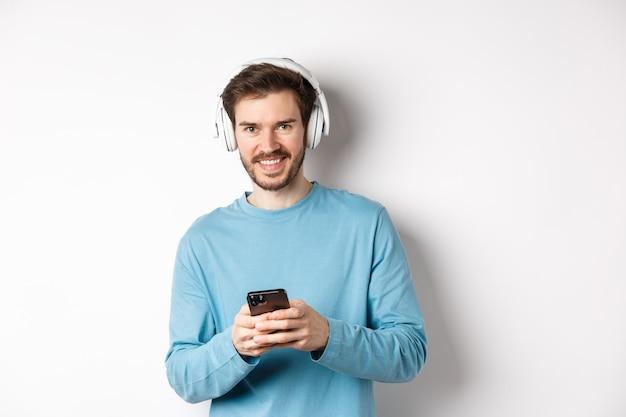 매력적인 웃는 남자는 무선 헤드폰으로 음악을 듣고 검은색 스마트폰을 사용하고 만족스러운 흰색 배경을 보고 있습니다.