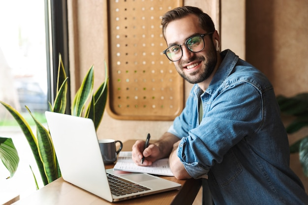 Attractive smiling man wearing glasses writing and using earpod with laptop while working in cafe indoors
