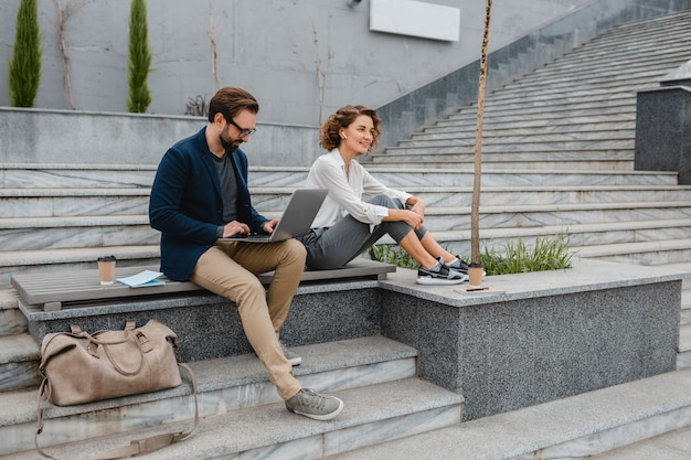 Attractive smiling man and woman sitting on bench in urban city center, making notes