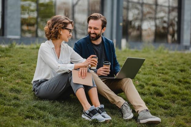 Attraente uomo e donna sorridenti che parlano seduti sull'erba nel parco urbano, prendendo appunti