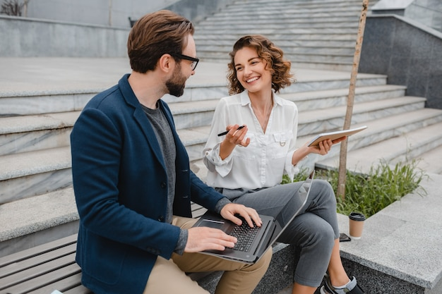 Attractive smiling man and woman talking sitting on stairs in urban city center, making notes