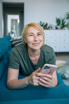 Attractive smiling middle age senior woman using smart phone while is lying on the sofa at home