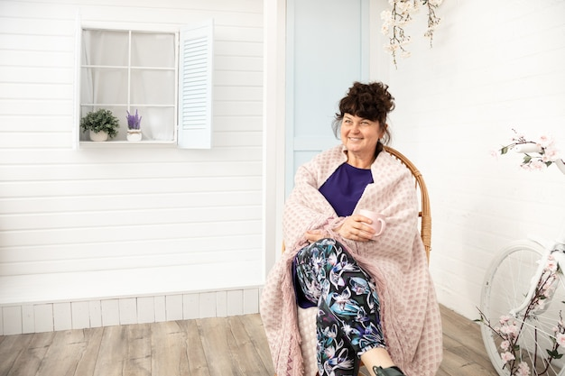 Привлекательная улыбающаяся женщина средних лет, сидящая в плетеном кресле на заднем дворе. летние, весенние каникулы за пределами города, воссоединение с природой. копия пространства.