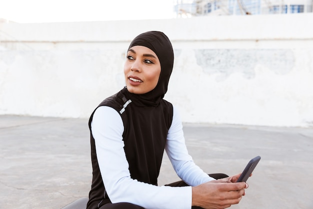 Attractive smiling muslim sportswoman wearing hijab outdoors, sitting on a fitness mat, using mobile phone