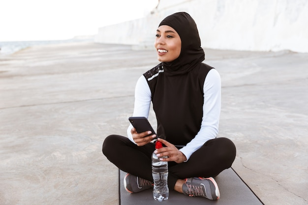 魅力的な笑顔のイスラム教徒のスポーツウーマン屋外でヒジャーブを身に着けている、水のボトルとフィットネスマットの上に座って、携帯電話を使用して