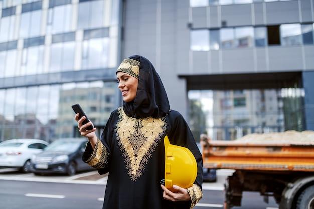 企業の建物の前に立って、スマートフォンを使用して、脇の下の下にヘルメットを保持している魅力的な笑顔のイスラム教徒の女性。女性も素晴らしい建築家になることができます。