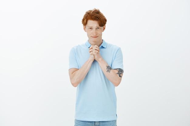 魅力的な笑顔の赤毛の男は、助けや恩恵を懇願し、嘆願で手を握り締めます