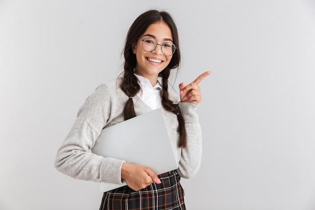白い壁の上に孤立して立っている、ラップトップを運ぶ、離れて指しているunifromを身に着けている魅力的な笑顔の女子高生