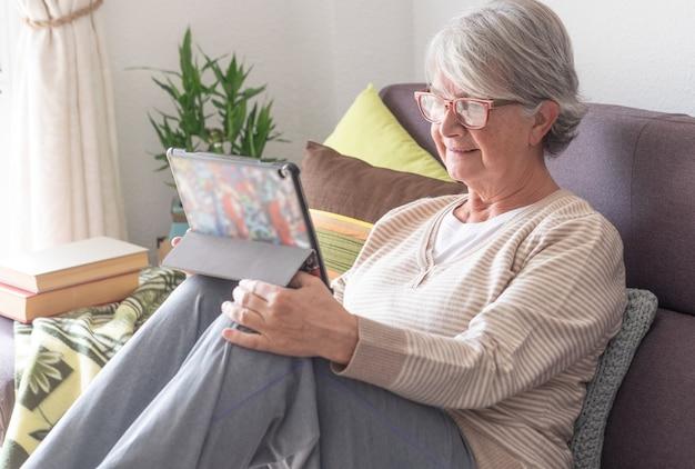 디지털 태블릿을 사용하여 집에서 소파에서 편안하게 웃는 매력적인 고위 여성. 창에서 밝은 빛