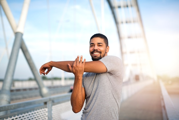 Attraente sportivo sorridente che riscalda il suo corpo per un allenamento all'aperto