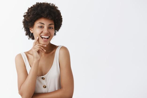 Attraente ragazza alla moda sorridente in posa contro il muro bianco