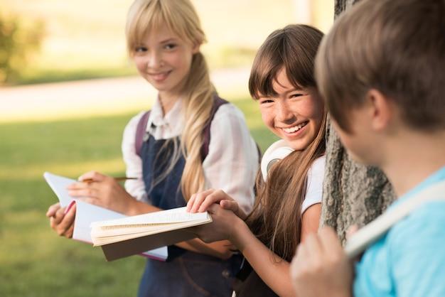Привлекательные улыбающиеся девочки-подростки вместе учатся в парке