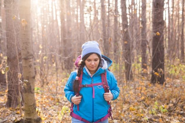 울창한 숲 속을 걷고 있는 매력적인 웃는 관광 여성.