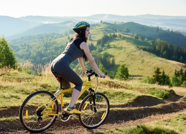 Attractive smiling woman biker riding on yellow bicycle on rural trail in the mountains, wearing helmet, on summer day.