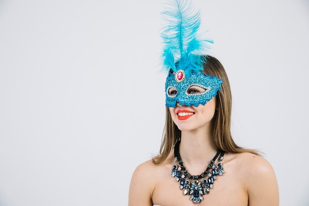 Attractive smiling woman in blue carnival feather mask on white backdrop