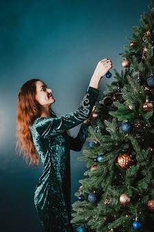 Attractive smiling woman decorating christmas tree