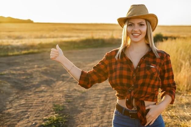 カウボーイスタイルに身を包んだ魅力的な笑顔の女性が車を止めようとします。ヒッチハイクまたはヒッピーの概念