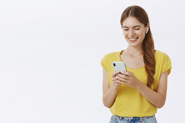 Attraente donna sorridente in cuffia ascoltando musica o podcast, utilizzando lo smartphone
